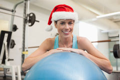 Fit smiling brunette in santa hat leaning on exercise ball Royalty Free Stock Photos
