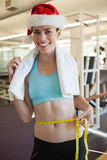 Fit smiling brunette in santa hat measuring her waist Royalty Free Stock Photos