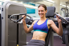 Fit smiling brunette using weights machine for arms Stock Images