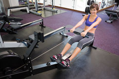 Fit smiling brunette working out on rowing machine Stock Images