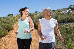 Fit smiling couple jogging down mountain trail Stock Images