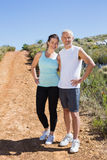 Fit smiling couple jogging down mountain trail Stock Photos