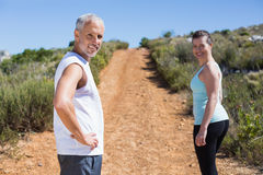 Fit smiling couple jogging up mountain trail Stock Images