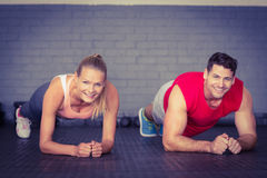 Fit smiling couple planking together in gym. In crossfit gym royalty free stock images