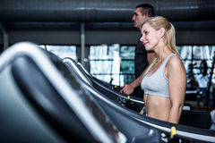 Fit smiling couple using treadmill Stock Image