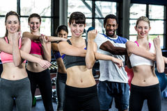 Fit smiling group doing exercise. In gym royalty free stock photos