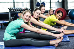 Fit smiling group doing stretching stock image