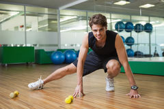 Fit smiling man warming up in fitness studio Stock Photography