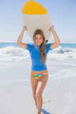 Fit smiling surfer girl on the beach with her surfboard Stock Images