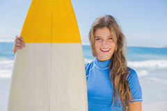 Fit smiling surfer girl on the beach with her surfboard Stock Photography
