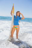 Fit smiling surfer girl standing on the beach with her surfboard Royalty Free Stock Images