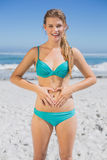 Fit smiling woman in bikini on the beach making heart shape on stomach Royalty Free Stock Photo