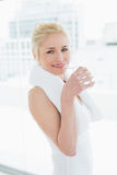 Fit smiling woman drinking water at the gym Stock Image