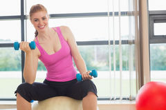 Fit smiling woman with dumbbells sitting on exercise ball Royalty Free Stock Photos