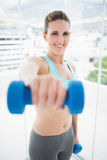 Fit smiling woman exercising with dumbbell Royalty Free Stock Photos