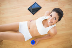 Fit smiling woman holding sports bottle lying on wooden floor Stock Photography