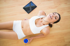 Fit smiling woman holding sports bottle resting Stock Photos