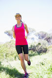 Fit smiling woman jogging Stock Photos