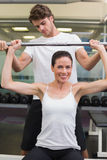 Fit smiling woman lifting barbell with her trainer spotting Royalty Free Stock Image