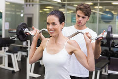 Fit smiling woman lifting barbell with her trainer Stock Images