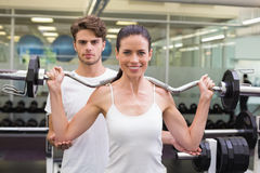 Fit smiling woman lifting barbell with her trainer Stock Photography