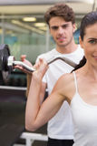 Fit smiling woman lifting barbell with her trainer Royalty Free Stock Photography