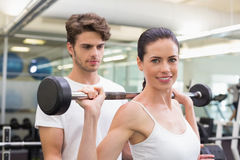 Fit smiling woman lifting barbell with her trainer Stock Image