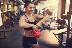 Woman practicing arm muscles with kettle bell weight in gym. Fit smiling woman practicing arm muscles with kettle bell weight in gym royalty free stock photos