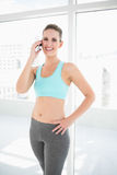 Fit smiling woman in sportswear talking on the phone Stock Photo