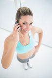 Fit smiling woman talking on mobile phone Royalty Free Stock Photography