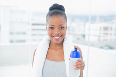 Fit smiling woman with towel around her neck holding sports bottle Stock Photography
