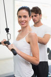Fit smiling woman using weights machine for arms with her trainer Stock Images
