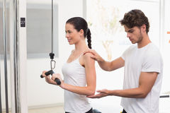 Fit smiling woman using weights machine for arms with her trainer Stock Photo