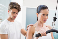 Fit smiling woman using weights machine for arms with her trainer Royalty Free Stock Photo