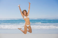 Fit smiling woman in white bikini leaping on beach Stock Images