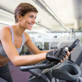Fit smiling woman working out on the exercise bike Royalty Free Stock Photography