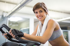 Fit smiling woman working out on the exercise bike Stock Photo