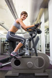 Fit smiling woman working out on the exercise bike Royalty Free Stock Photo