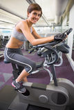 Fit smiling woman working out on the exercise bike Stock Image