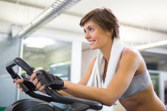 Fit smiling woman working out on the exercise bike Stock Images