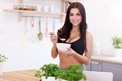 Fit smiling young woman with bowl of corn flakes in modern kitchen Royalty Free Stock Photography
