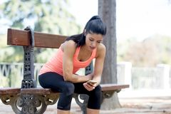 Fit sport woman looking at mobile phone internet app tracking performance after running workout sitting on park bench happy. Young beautiful and fit sport woman Royalty Free Stock Images