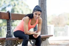 Fit sport woman looking at mobile phone internet app tracking performance after running workout sitting on park bench happy Stock Photography