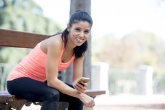 Fit sport woman looking at mobile phone internet app tracking performance after running workout sitting on park bench happy Stock Photo