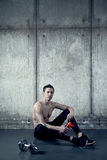 Fit sportive muscular man seating on floor with water Royalty Free Stock Photography