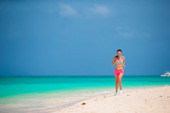 Fit sports young woman running along tropical beach in her sportswear Royalty Free Stock Photography