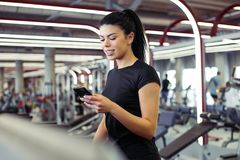Young Sportswoman using smartphone while jogging on treadmill. Fit Sportswoman using smartphone for training workout app while jogging on treadmill Royalty Free Stock Image