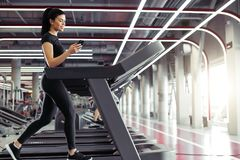 Young Sportswoman using smartphone while jogging on treadmill. Fit Sporty business woman texting on smartphone while jogging on treadmill Royalty Free Stock Photo