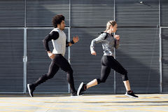 Fit and sporty couple running in the street. Royalty Free Stock Photo