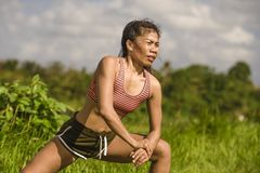 Fit and sporty middle aged runner Asian woman stretching leg and body after running workout on green field beautiful background in royalty free stock photos